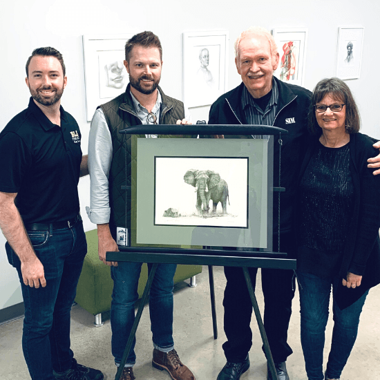 Alumnus Jim Rendel with wife Sandy and a piece of his artwork
